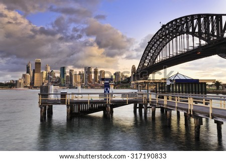 Close up view from wooden ferry pier to distant Sydney City CBD skyscrapers and arch of Harbour Bridge near sunset