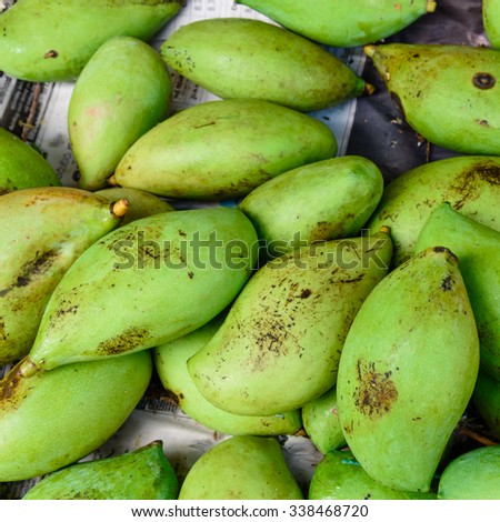 Close-up view group of fresh organic raw green Mangoes on display at Vegetable and Fruit Stall of Local Market at Little India, Singapore. Colourful fruit background and healthy concept  - stock photo