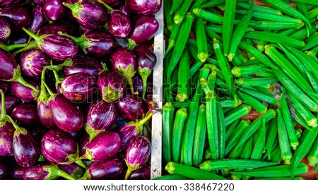 Close-up view group of fresh organic ripe Eggplant (or Brinjal) and Okra (or Lady Finger) on display at Vegetable and Fruit Stall of Local Market at Little India, Singapore. Colorful, healthy concept - stock photo