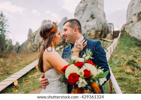 Close up view handsome groom in stylish blue suit kissing white dressed bride holding bouquet of roses on majestic mountain landscape with big rocks as backround