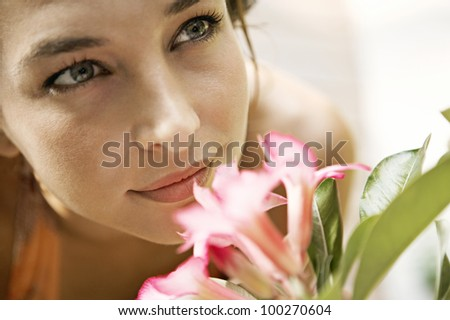 Close up view of a beautiful young woman smelling a pink flower and smiling.