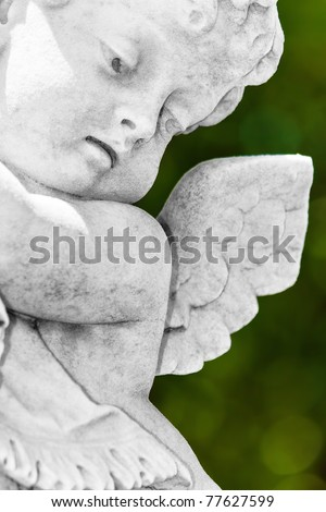 Close up view of a black and white  infant angel or cherub  statue with a diffused green vegetation background - stock photo