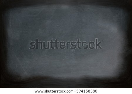 Close up view of a black dirty chalkboard without a wooden frame. Chalk on the blackboard has been rubbed out. Primitive teaching style. Background texture and empty space for further creative design. - stock photo