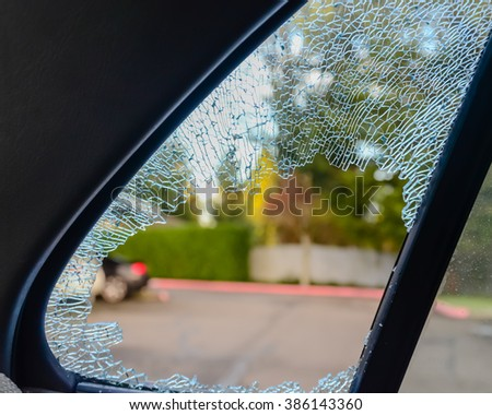 Close-up view of a broken passenger window car smashed by a thief. Damaged glass from car theft. - stock photo
