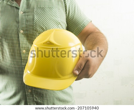 Close up view of a business man carrying a yellow hardhat under his arm, Empty copyspace textured wall wiht wallpaper for inscription - stock photo