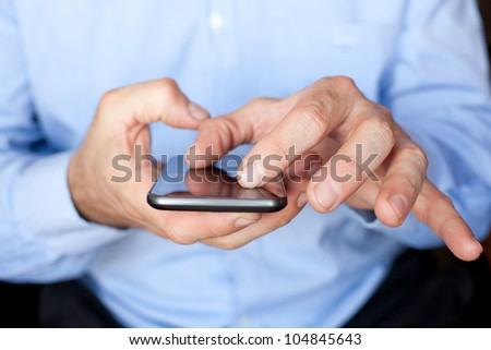 Close up view of a businessman using multi gestures on a smartphone to zoom in a document