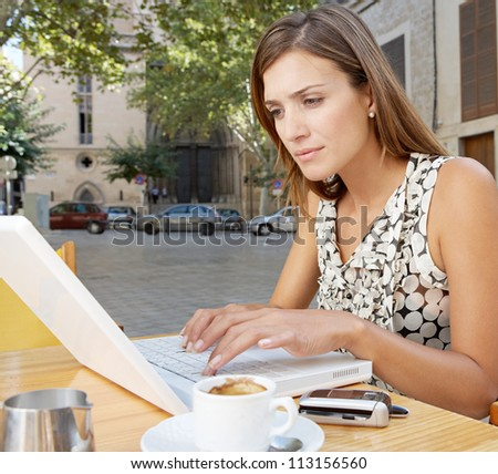 Close up view of a businesswoman using a laptop computer while having a coffee in a coffee shop terrace, outdoors.