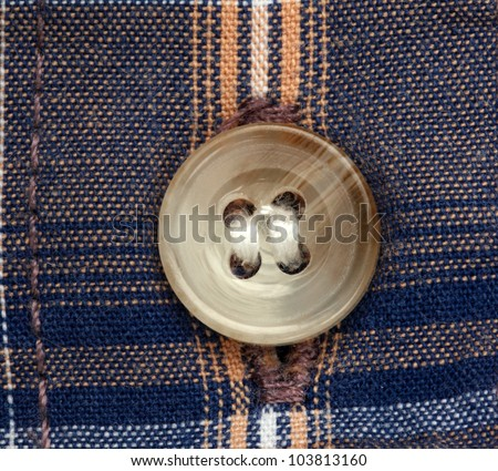 Close up view of a button over checked shirt - stock photo