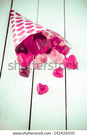 Close-up view of a candy cone decorated with pink hearts spilling heart shaped gummy candies over a white wooden board table - stock photo