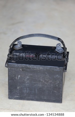 Close up view of a car battery sitting on the ground. - stock photo
