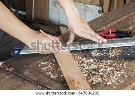 Close Up view of a carpenter using a pencil to draw a line on a wooden