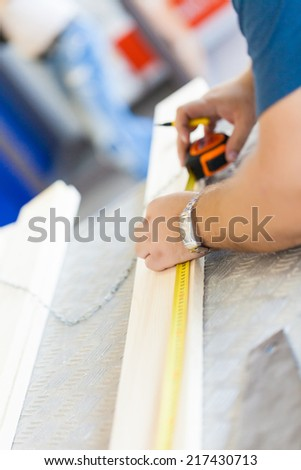 Close Up view of a carpenter using a straightedge to draw a line.