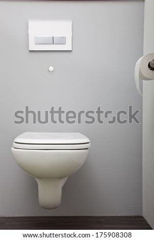 Close up view of a closed wall mounted toilet with a concealed cistern in a plain white bathroom
