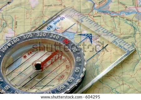 Close-up view of a compass sitting on a topo map. - stock photo