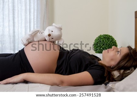 Close up view of a expecting pregnant woman with a stuffed toy. - stock photo