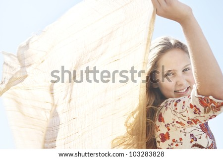 Close up view of a girl holding fabric in the air and smiling at the camera. - stock photo
