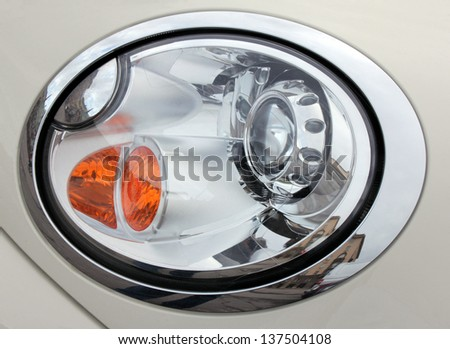 Close up view of a headlight of elegant car. - stock photo