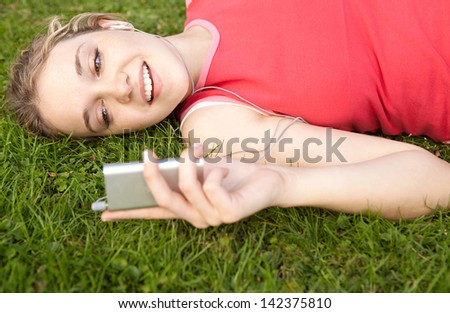 Close up view of a joyful young woman laying down on a park green grass, taking a break from exercising while listening to music with her mp4 player and earphones, smiling. - stock photo