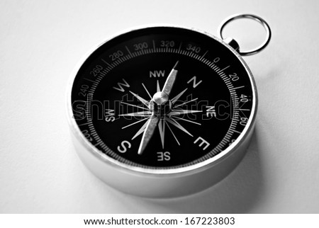 Close up view of a magnetic handheld compass with copyspace showing the needle, compass rose and cardinal points conceptual of planning, navigation, discovery, travel and strategy