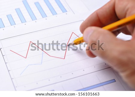 Close up view of a male hand holding a pencil analysing a fluctuating bar graph showing business performance