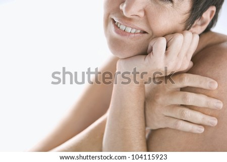 Close up view of a mature nude woman against a white background, smiling.