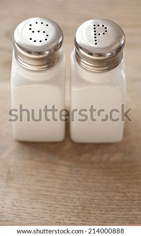 Close up view of a pair of salt and pepper dispensers standing together on a wooden table in a restaurant, interior. Still life cooking and food serving objects.
