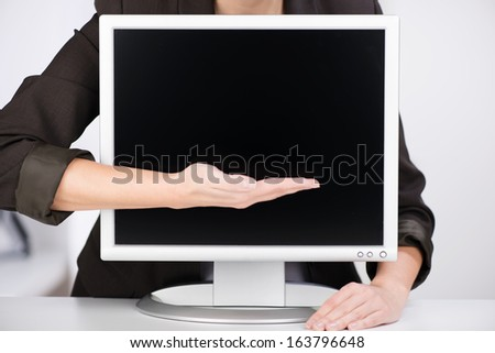 Close up view of a professional business woman pointing to a blank computer monitor with her hand presenting blank copyspace for your text - stock photo