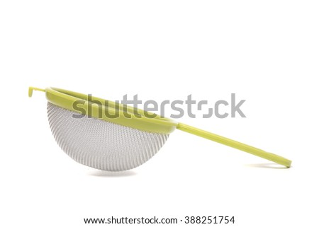 Close up view of a round metal strainer isolated on white background.