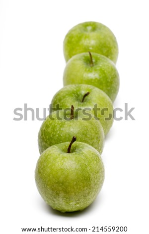 Close up view of a row of green apples isolated on a white background. - stock photo