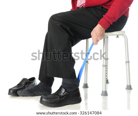 Close-up view of a senior man sliding into his loafers with the aid of a long-handled shoe horn.  On a white background. - stock photo