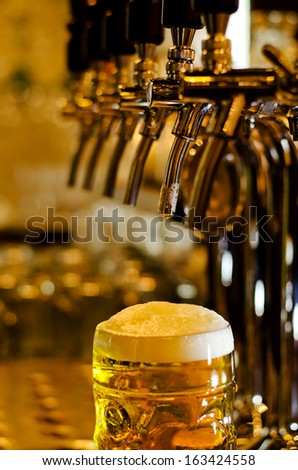 Close up view of a tankard of beer with a frothy white head standing on a bar counter in a pub with selective focus to the glass - stock photo