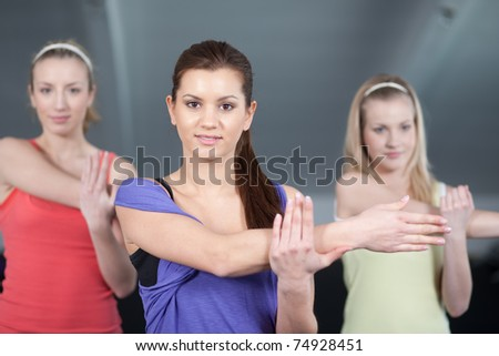 Close up view of a three beautiful young women stretching in a health club - stock photo