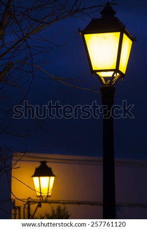 Close up view of a traditional european streetlight pole lit at night.