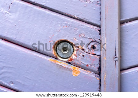 Close up view of a wall wooden with blue paint and keyhole