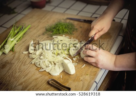 Close up view of a woman chopping fennel on a cutting board in a kitchen