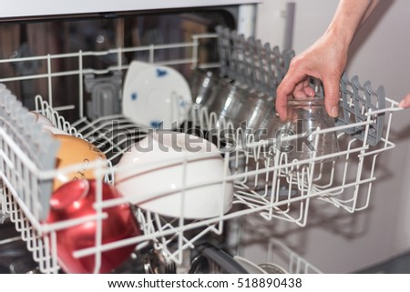 Close up view of a woman hand loading the dishwasher. Shallow dof, selective focus on the hand.