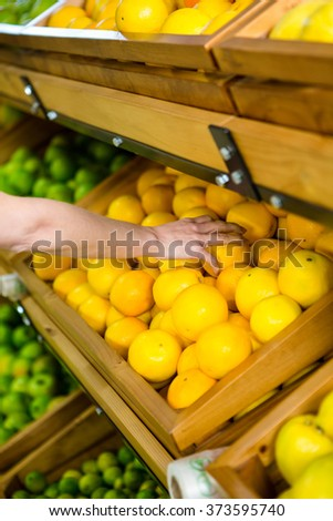 Close up view of a woman picking orange in supermarket