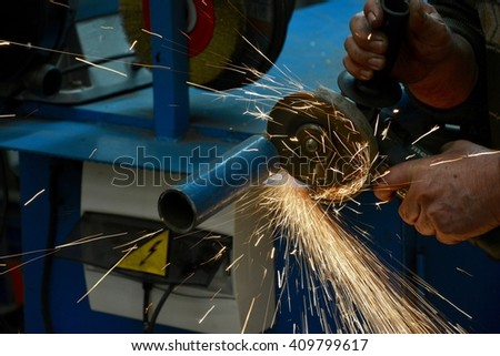Close up view of a worker's hands using a radial saw.