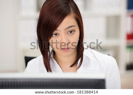 Close up view of a young Asian businesswoman hard at work sitting at her desk reading the screen of her desktop monitor - stock photo