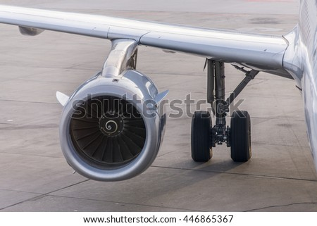 close up view of airplane turbine engine, wing and wheel of airplane.