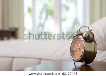 close up view of alarm-clock in morning bedroom environment - stock photo