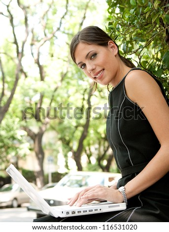 Close up view of an attractive businesswoman using a laptop computer while sitting in a leafy city street during a sunny day, smiling. - stock photo