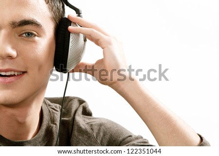 Close up view of an attractive young man's half face listening to music with his headphones, isolated against a white background. - stock photo
