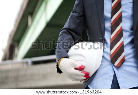Close up view of architect holding helmet standing under highway construction - stock photo