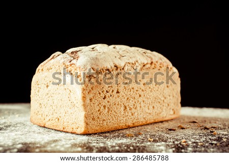 Close Up View of Artisinal Loaf of Whole Wheat Bread on Flour Covered Surface with Black Background - stock photo