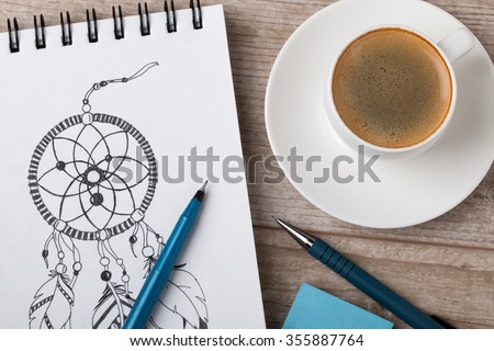 Close-up view of artist's or designer's table. Cup of coffee, pencil, fine liner and eraser laying on sketch book with hand-drawn dream catcher - stock photo