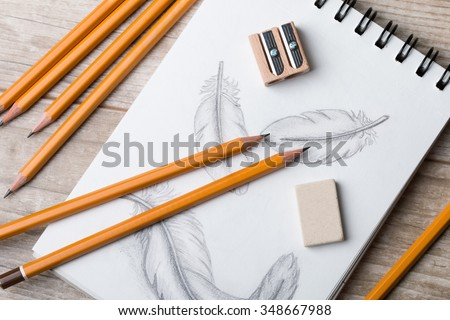 Close-up view of artist's or designer's table. Pencils, sharpner and eraser laying on sketch book with hand-drawn feathers - stock photo