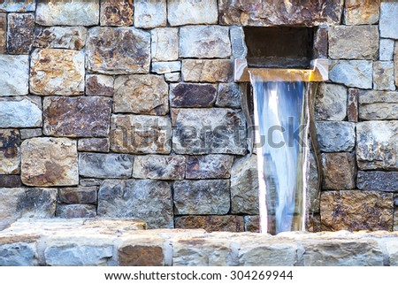 Close-up view of artistic water fountain with vibrant stone wall, shallow DOF - stock photo