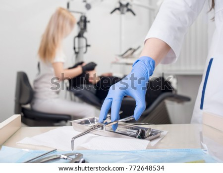 Close-up view of assistant's hands with blue gloves working with dental equipment, on the blurred background female dentist is treating patient in dental office. Dentistry