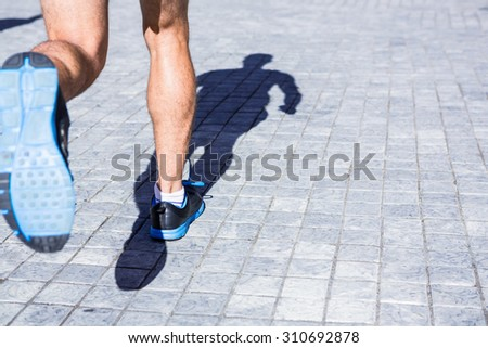 Close up view of athletes legs running in the city - stock photo